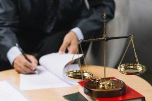 un homme qui rédige un document près de la balance de la justice