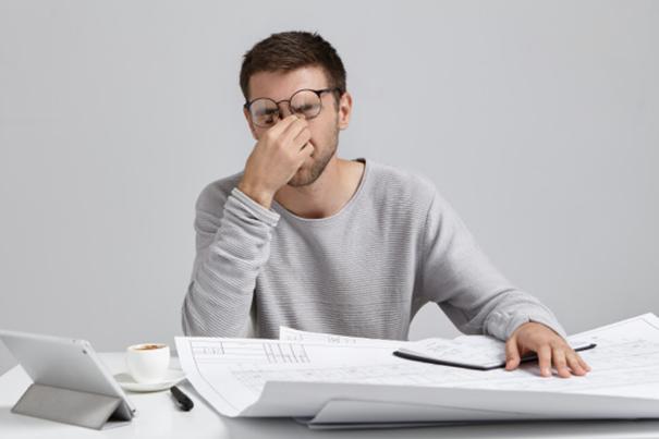 un homme en train de travaillé et qui semble très fatigué ou en situation de détresse